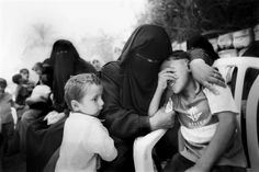 A mother comforts her young boys during a funeral for one of her other sons who was shot and killed while sleeping in his Khan Younis home in the Gaza Strip in May 2004. Photo credit: Benedicte Kurzen