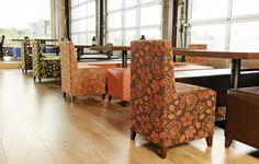In einem hochfrequentierten Restaurant sind gepolsterte Sitzwürfel mit Rückenlehne eine platzsparende Alternative zu ausladenden Holzstühlen oder Sesseln.