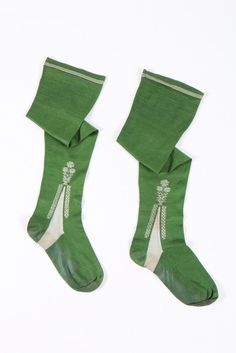 A pair of frame-knitted green silk stockings, English or French, 1750-70. A pair of frame-knitted green silk stockings, English or French, 1750-70. the ivory clocks edged with diapered bands and pots of blooms, striped upper edge