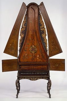 "Clavicytheria, or upright harpsichords, were made as early as the 15th century, but tall examples such as this date from the late Baroque era. Having 2 sets of doors that conceal the strings, the case appears ungainly when open, but when closed it has a graceful outline embellished by gilded ""wings"" and stops control 2 sets of strings. The mechanism has been altered and the painted soundboard is a replacement; originally the instrument may have been an upright piano."