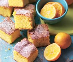 Squares of gluten free clementine cake dusted in icing sugar and served with slices of orange