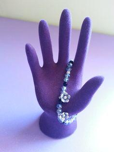 Pulsera de piedras transparentes y negras con un par de flores de plata. Perfecta para cualquier ocasión.