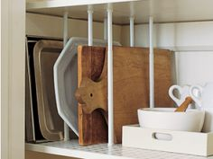 re-use some tension style curtain rods that will fit the height of your kitchen cabinets. Position them in pairs, front to back, at intervals that will hold your bakeware, chopping boards, trays and heavy platters. This will keep them upright and means you don't have to lift the whole stack each time you need one at the bottom.