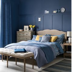 Create a gentle look in a bedroom scheme by teaming a deep indigo blue with purplish cornflower tones, adding textured woods and pelnty of soft textiles for a comfortable, lived-in look