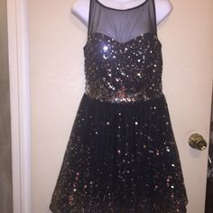 Rue 21 sparkly dress with sheer net bodic 100% polyester sparkly dress with sheer black netting on bodice. Has a zipper in back of dress . Rue 21 Dresses Prom