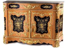 Enchanting Napoleon III style ormolu-mounted veneer inlaid and hand painted side cabinet, after the model Circa 1860, surmounted by a serpentine stepped black marble top above a frieze ormolu band large drawer centered by foliate acanthus mount, flanked to each side by a floral painted panel with ormolu foliate handle, above a pair of cupboard doors, each centered by a cartouche with spring flowers with a scroll and foliate frame, the interior fitted with .. www.antiquetaste.com