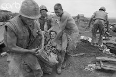 04 Oct 1967, Corn Thien, South Vietnam --- Three Marines gently lift a badly wounded and pained buddy following a Communist bombardment of this battered hill outpost two miles south of the Demilitarized Zone. Military sources reported that the Marines, Backed by massive American firepower, have won the battle of Con Thien. The battered Communist troops massed in the DMZ were reported pulling back into North Vietnam Oct. 4th, taking their guns with them.
