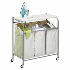 "Dual-purpose laundry center with a 3-compartment hamper with removable laundry bags. Includes a flip-up top ironing board with cotton cover.   Product: Laundry centerConstruction Material: Metal and cottonColor: White and silverFeatures:  Three compartments for sortingThree removable laundry bagsFlip-top ironing board Wheels for easy transporting Dimensions: 33"" H x 31"" W x 16"" D"
