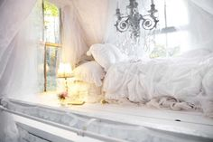chambre bohème blanche avec une atmosphère romantique, une literie blanche et un lustre vintage décoré de pampilles