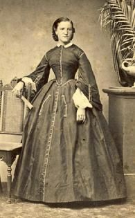 1861-1865, Lovely 2-piece tea gown with tabbed, pagoda sleeves, full undersleeves, removable collar & a pleated skirt with trimmed pockets.  And surprisingly the lady's hair is parted on the side rather than in the middle.