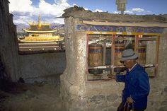 The Gelugpa monastery of Tashilhunpo, Tibet.  Pilgrim turning prayer wheel