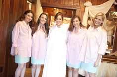 Bride and bridesmaids wearing button-down shirts over dresses
