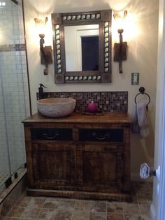 Love this old world style bathroom.  The wooden mirror, wooden vanity and wall sconces really add ambiance.