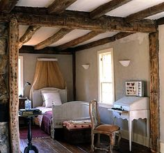 Beautiful beamed ceiling and wood floor in the bedroom of a French gite.