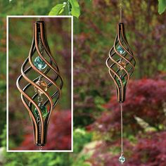 """Watch this kinetic copper-finished wind sculpture as it gracefully spins in the wind. The twisted cage holds 3 iridescent marbles with 1 additional marble that swings from the metal chain for a stunning visual effect. 22"""" long, ready to hang."""