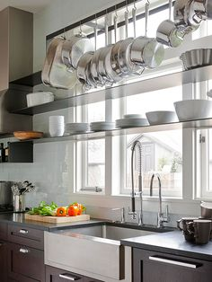 Natural light is a boon in small spaces, helping to brighten dark corners and make tight rooms feel bigger. But windows can also gobble up potential storage spots. To get the best of both window-focused worlds, consider a strategy used in this kitchen: a mid-height shelf for a few short bowls, and a hanging rack near the ceiling for essential pots and pans.