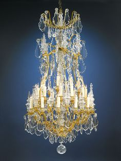 This Baccarat crystal and doré bronze chandelier is a grand sight to behold. Hundreds of beautifully designed oversized, luminous prisms and beads of hand wood-polished baccarat crystal hang from scrolling branches of doré bronze. This 30-light fixture is of exceptional quality and boasts some of the finest crystal in the world.