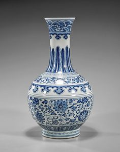 Tall Qianlong-Style Blue & White Bottle Porcelain Vase, of globular body an tall flaring neck, depicting scrolling peonies, chrysanthmums and lotus flowers to the body; several decorative bands to neck, shoulder and base; seal mark; H: 15 1/2""