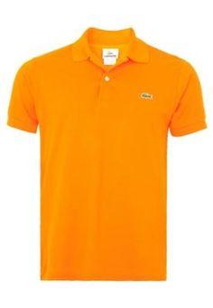 Camisa Polo Lacoste Read laranja, com bordado da marca na parte frontal. Conta com manga curta e barra com abertura lateral. Confeccionada em malha piquet, para um caimento acentuado e toque texturizado. A Camisa Polo Lacoste Read é ideal para o dia a dia.