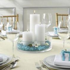 Centro de mesa para bautizo, con velas en blanco y azul.