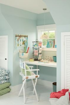 Pale blue walls and louvered closet doors flank a nook turned desk area with white built-in desk under window lined with a white directors chair illuminated by a contemporary white pendant.