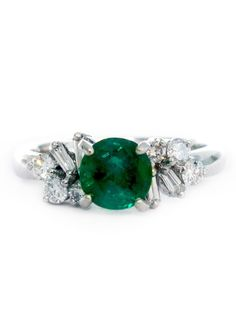 Laverna is a truly unique engagement ring with timeless details and luxurious diamond flourishes. Her striking emerald center stone features a classic green hue and is approx. 1 carat. A cluster of sleek baguettes and round diamonds add distinctiveness and balance. This extraordinary engagement ring is an antique treasure, destined to become an heirloom for generations to come. One of a kind.