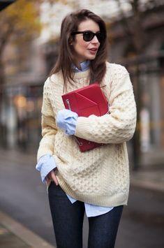 Den Look kaufen: https://lookastic.de/damenmode/wie-kombinieren/strickpullover-hellbeige-bluse-mit-knoepfen-hellblaue-enge-jeans-dunkelblaue-clutch-rote/1138 — Hellbeige Strickpullover — Rote Leder Clutch — Hellblaue Bluse mit Knöpfen — Dunkelblaue Enge Jeans