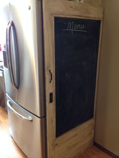 Old door with chalkboard to hide side of refrigerator ... What A Great Idea!