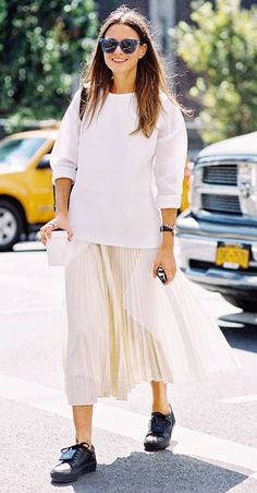 Simple white crewneck sweatshirt paired with a long ivory pleated skirt and black sneakers accessorized with blue frame sunglasses