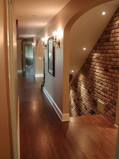 Basement entrance-no door, lights on the roof leading down the stairs highlighting the wall.