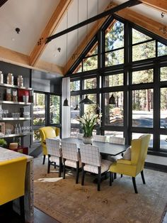 The kitchen flows straight into the dining room — a floor plan ideal for entertaining. To unify the two spaces, designer Linda Woodrum used the same yellow leather from the kitchen's bar stools on the dining room's wingback chairs.  http://www.hgtv.com/dream-home/dining-room-pictures-from-hgtv-dream-home-2014/pictures/index.html?soc=pindhm