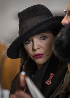 Joan Collins wearing a Philip Treacy hat at Baroness Thatcher funeral.