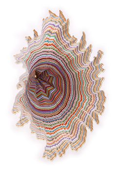Jen Stark fait des piles de feuilles de papier et les découpes pour révéler des couches multicolores.