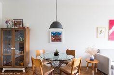 Sala de jantar tem cristaleira de madeira, mesa com tampo de vidro e pendente cinza.