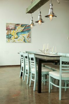 Minimal Coastal Dining Room with painted cottage chairs and brushed green wood beams.