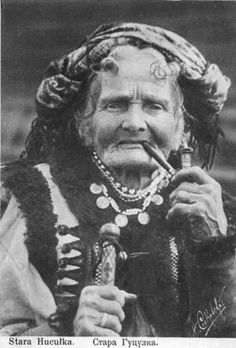 Classic photograph of an older Hutsul woman smoking a pipe.