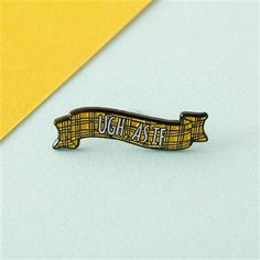 Part of our enamel pins range, this pin is in the shape of a banner which reads 'Urh, as if'.
