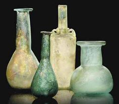 A ROMAN GREEN GLASS UNGUENTARIUM   CIRCA 4TH CENTURY A.D.  [I just like the composition of this photo]