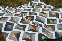 The Prism quilt pattern is a simple yet bold paper pieced quilt pattern. The quilt uses a variety of shades of grey and a rainbow of bright colors.