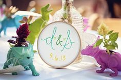 Fun and cute way to incorporate adrian into the wedding as well, since he is a part of the family that is being made... using little plastic painted dinosaurs as plant holders...