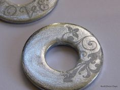 Washers decorated with nail polish and rub ons. Amazing!  What a fun addition to a jewelry piece!