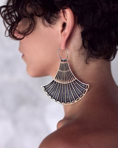 The unusual shape of the earring is based on a form found often in Egyptian hieroglyphics. It is the blue lotus flower rendered in an art deco style. The blue l