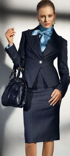 Office chic. Navy pinstripe suit w/blue blouse tied at the neck.