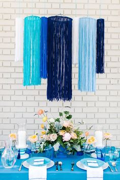 This chandelier-like hanging (made of yarn - how fab!) brings texture and movement to this outdoor tablescape.