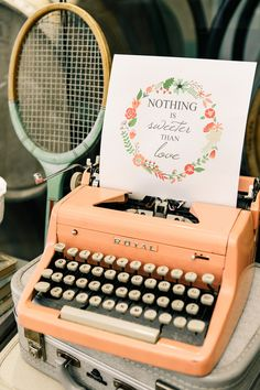 Colorful vintage typewriter makes for a playful sign holder Photo by Kings + Queens