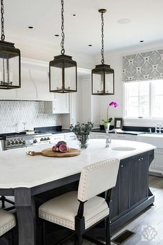 Three seeded glass lanterns hang over a black oval island topped with a honed white marble countertop seating white leather counter stools accented with a nailhead trim.