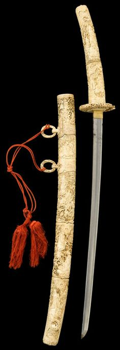 Japanese katana with ornate and impressive elephant ivory mounts. The edo period katana set in elaborately carved ivory handle showing buddhist figures among swirling clouds and scrollwork, with partial openwork ivory tsuba; the scabbard similarly carved and with two ring handles.