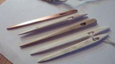 Kuparista, puusta ja poronluusta tehtyjä kinnasneuloja.
