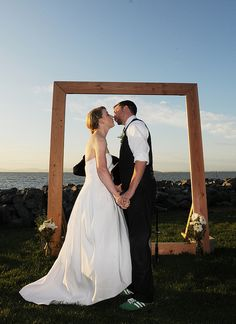 Build a wedding arch that doubles as a picture frame. I would add like greenery or birch(is that what its called?) and wrap it around the frame.