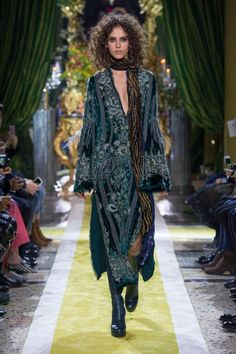 Roberto Cavalli AW16. A female model wearing an emerald, embroidered velvet kafkan, with a black and gold animalier print, beaded scarf, and green python print high-heeled, knee high boots